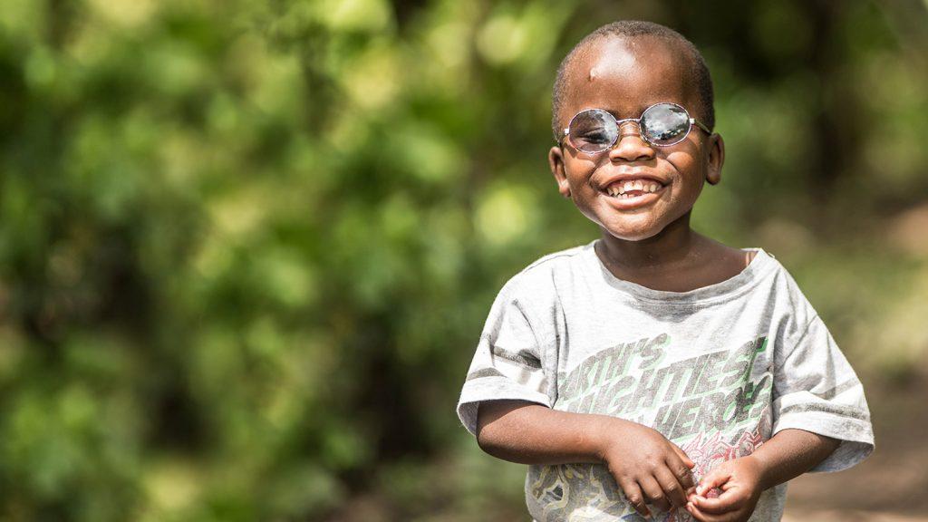 Criscent ler stolt i sina nya glasögon. Han står vid skogskanten utanför sin hemby i Uganda.