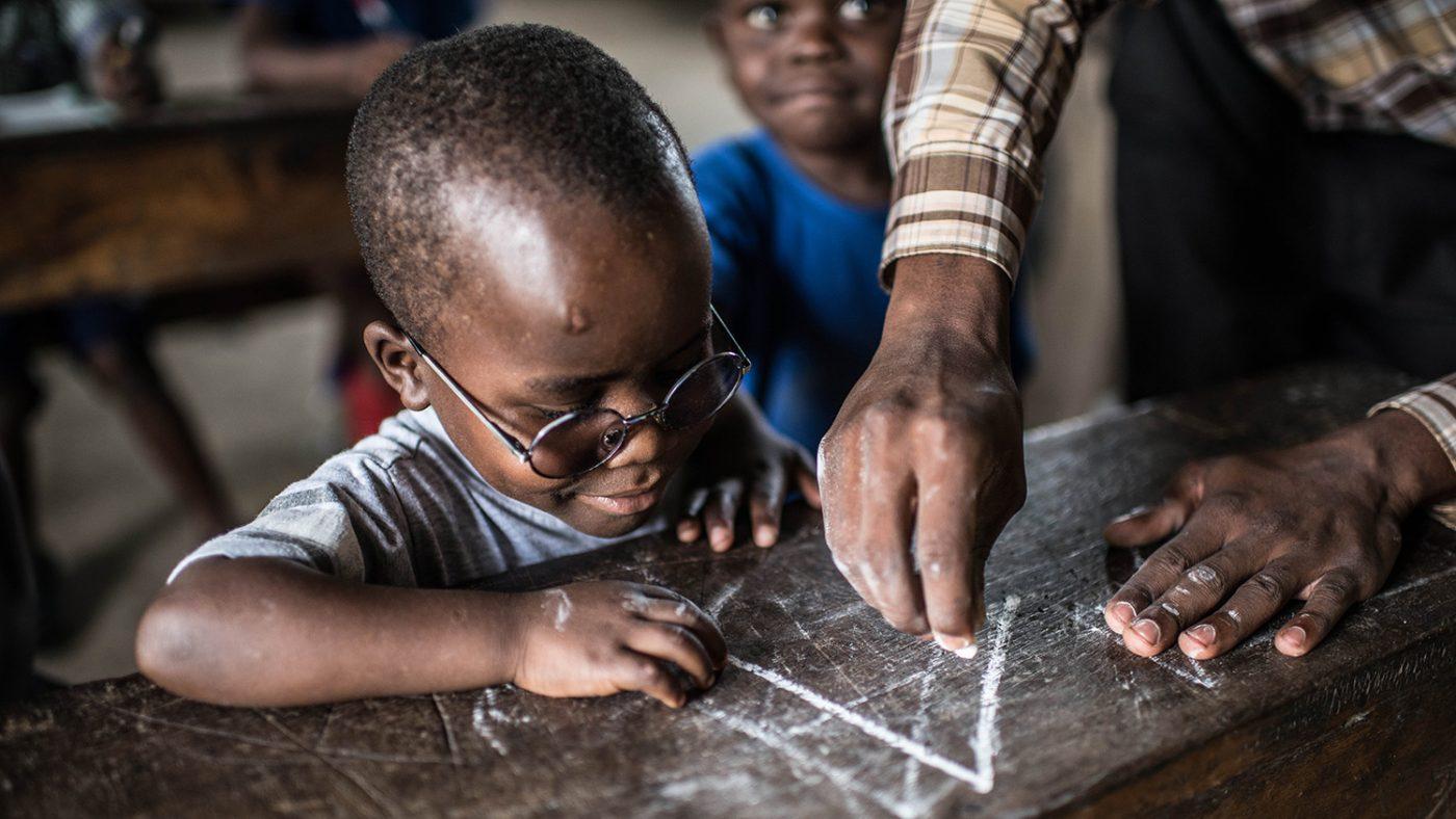Criscents lärare visar honom hur man skriver bokstaven A med en krita.