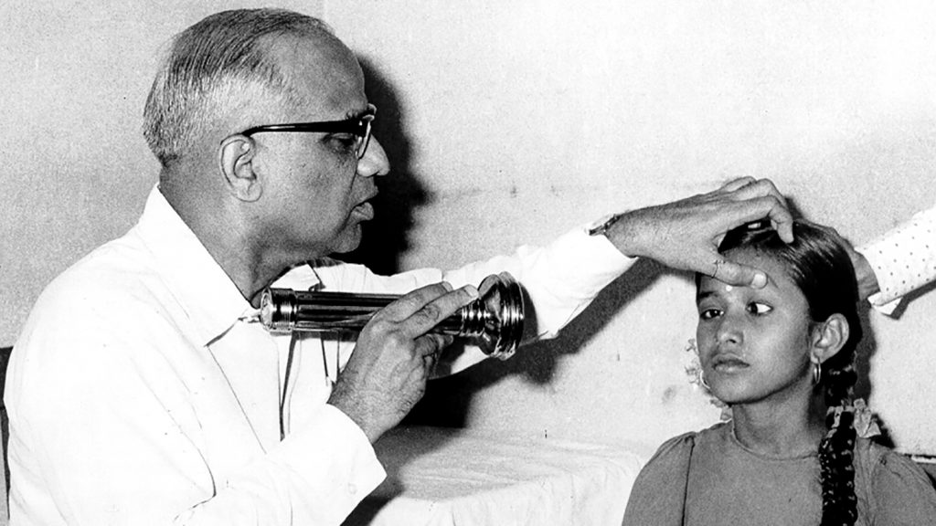 En läkare undersöker ögonen på en flicka i Indien på 50-talet.