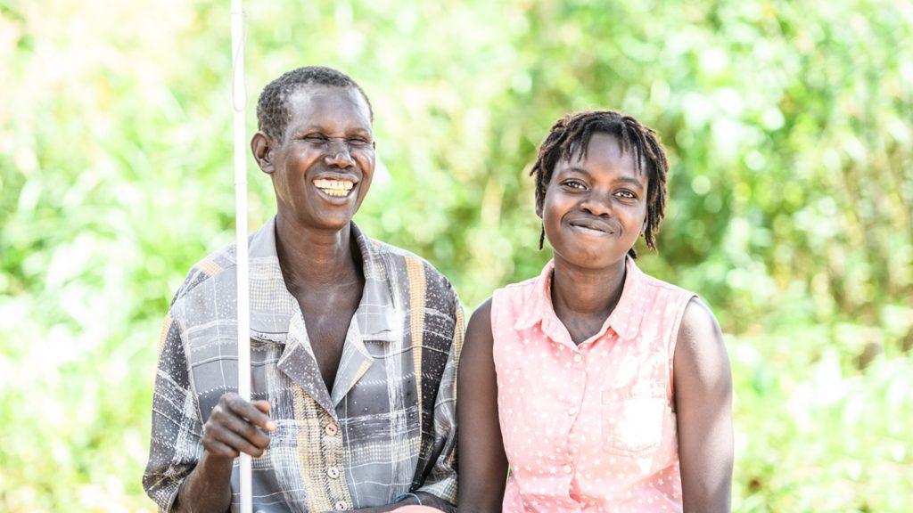 Ayenyo står bredvid Lawino och båda ler in i kameran.