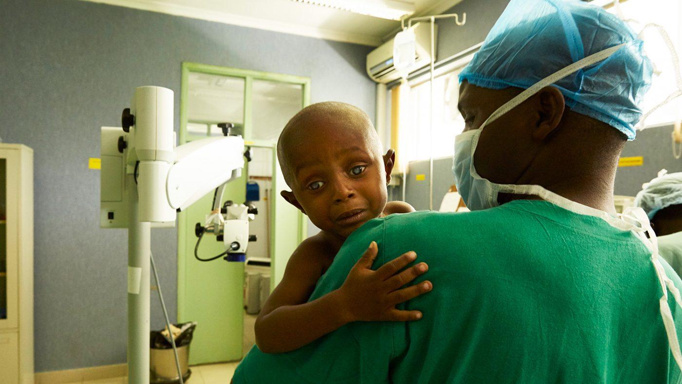 Baraka är rädd inför operationen och håller sig hårt fast i sköterskans famn.
