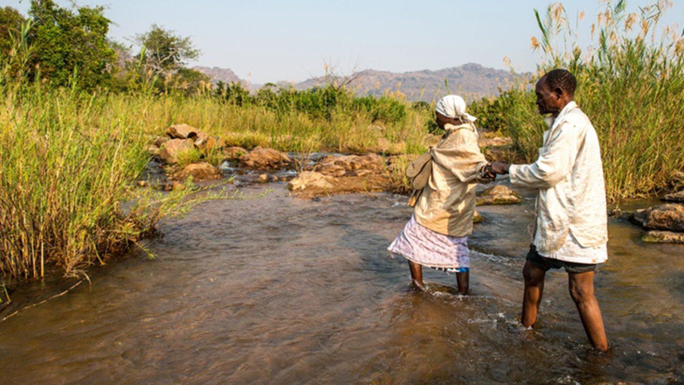 En blind man hjälps av sin fru att korsa en flod.