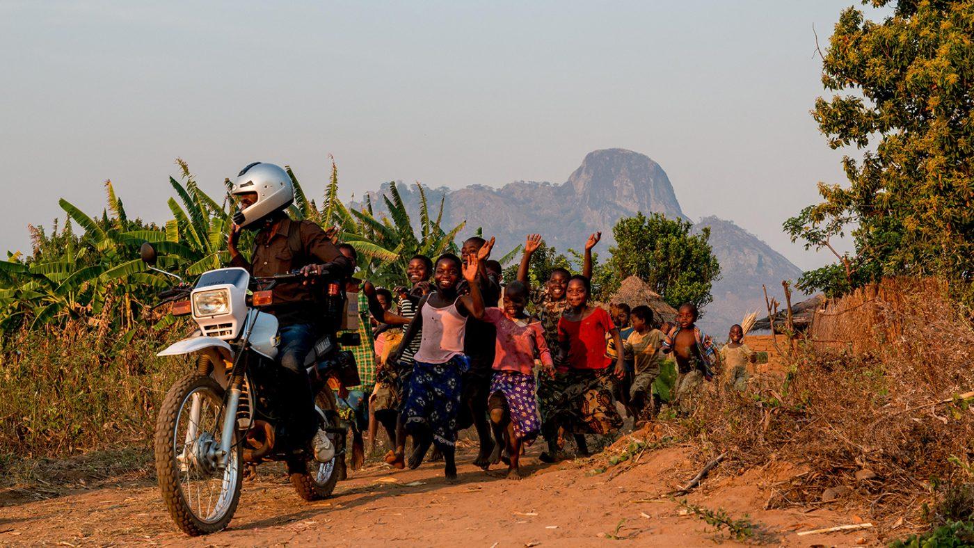 Madalitso Nyangulu kör sin motorcykel och en grupp barn springer glatt bakom honom.