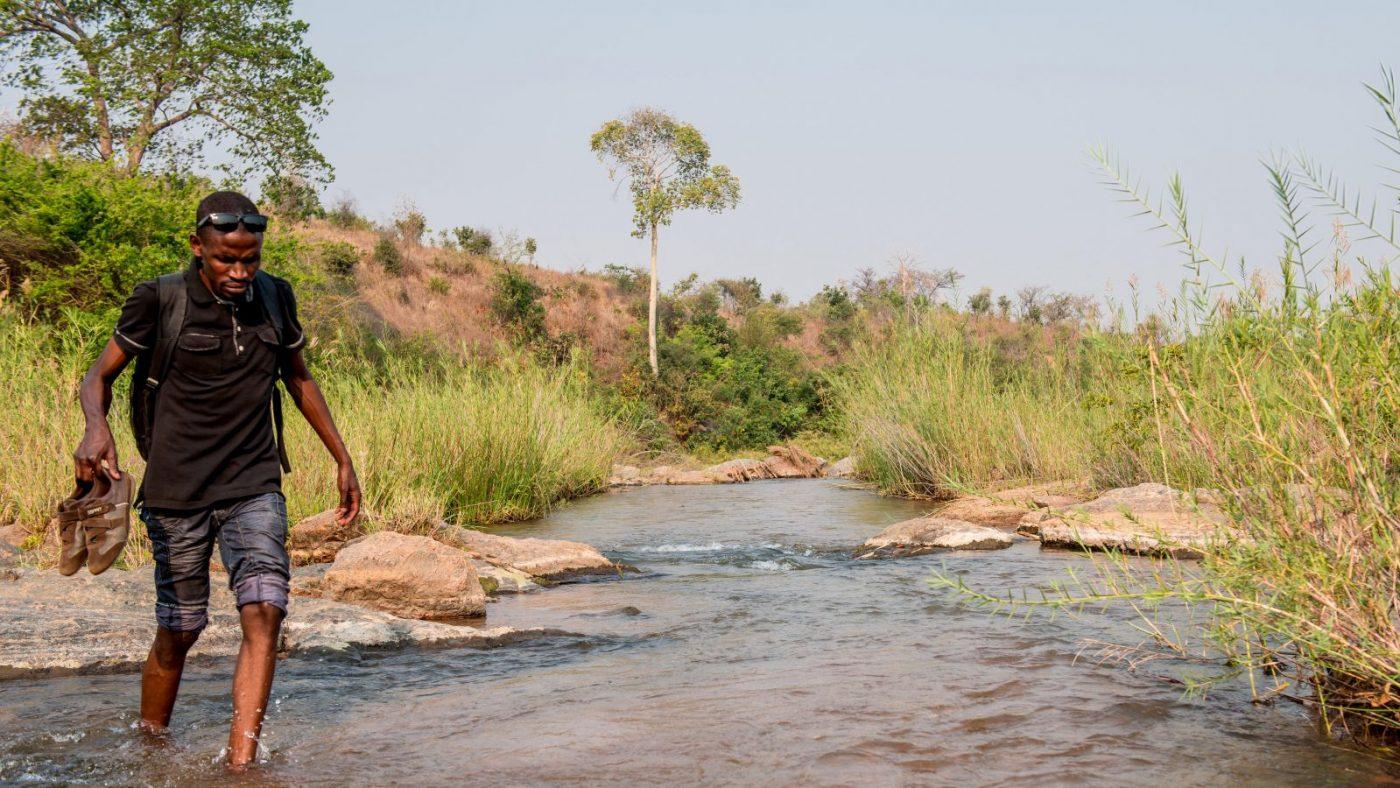 Madalitso Nyangulu går över en bäck.