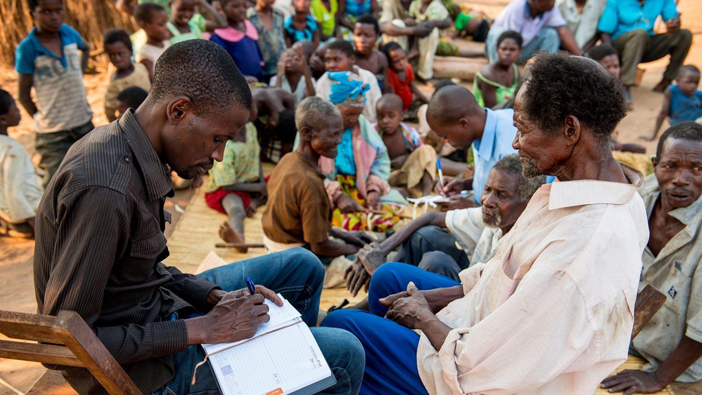 Madalitso Nyangulu sitter med en man och för anteckningar.