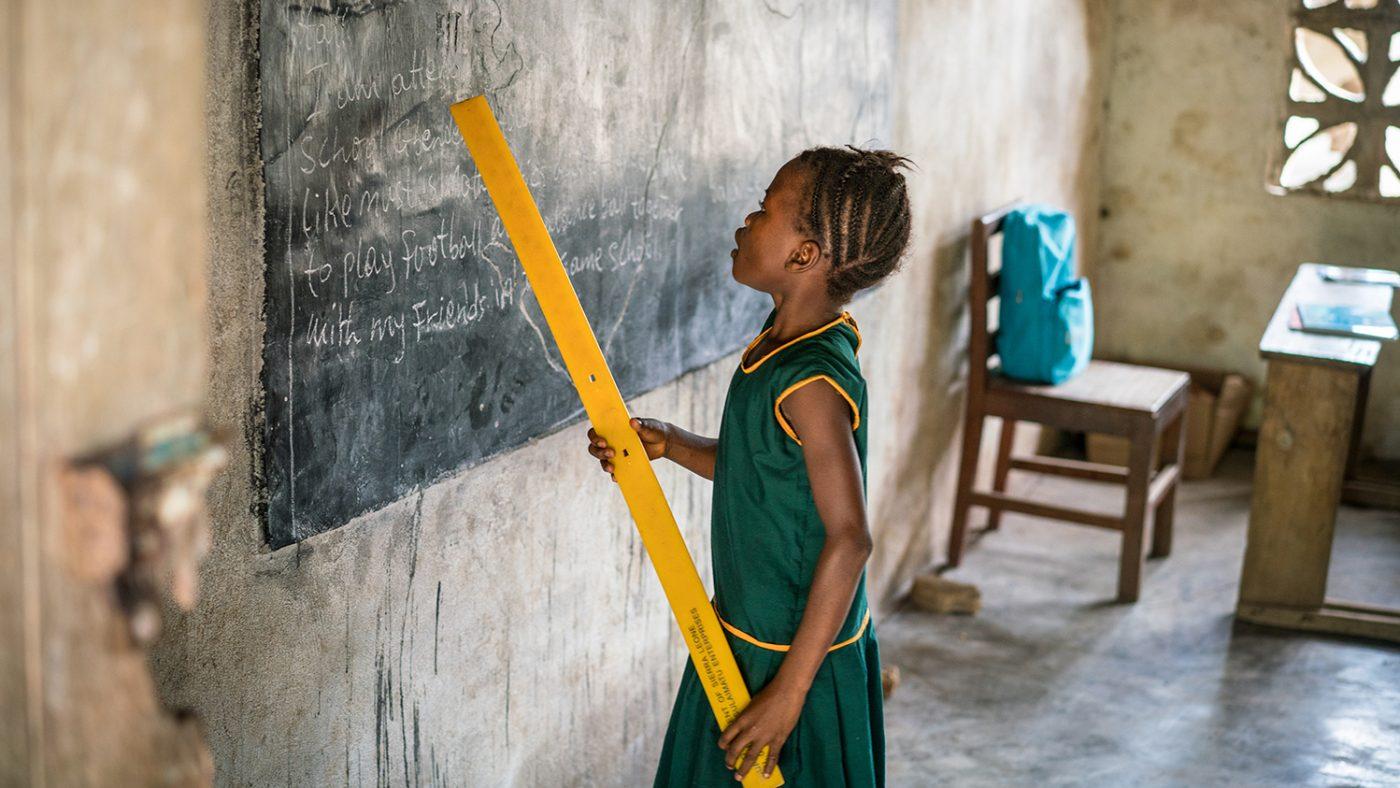 Aminata står vid svarta tavlan, hon håller en linjal för att peka på orden.