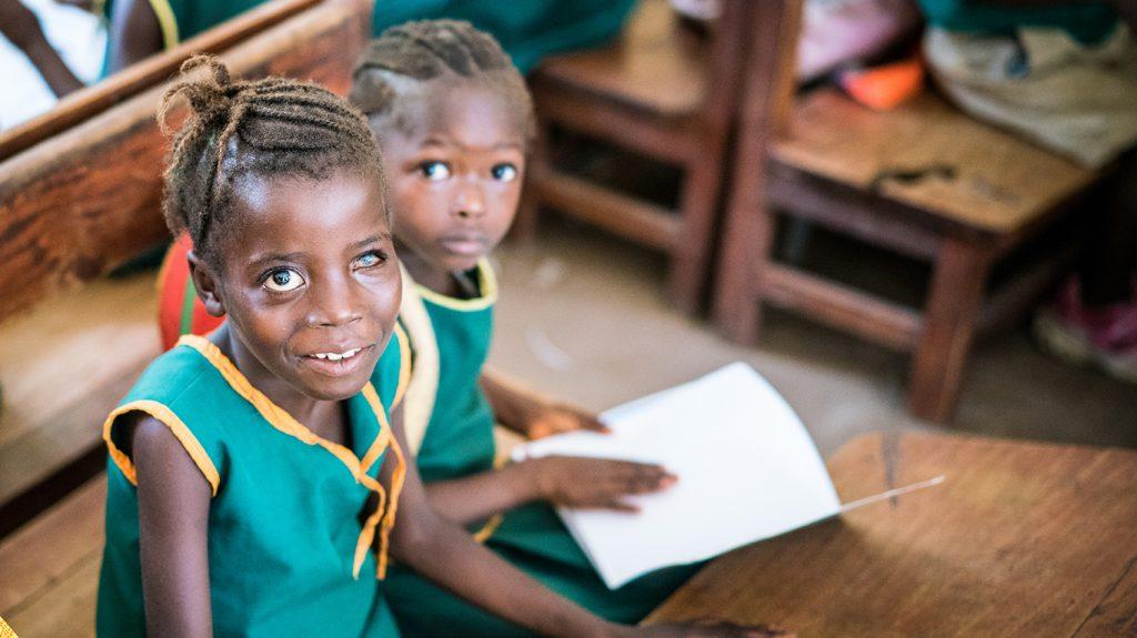 Aminata, som har nedsatt syn, sitter vid sin bänk bredvid en skolkamrat.
