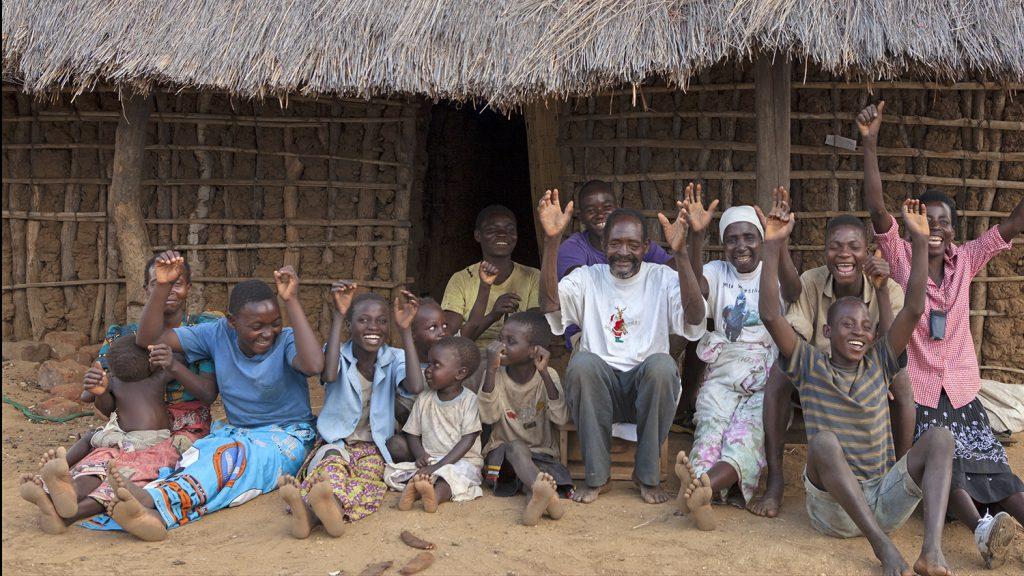 Winesi ler tillsammans med sin familj utanför deras hus i Malawi.