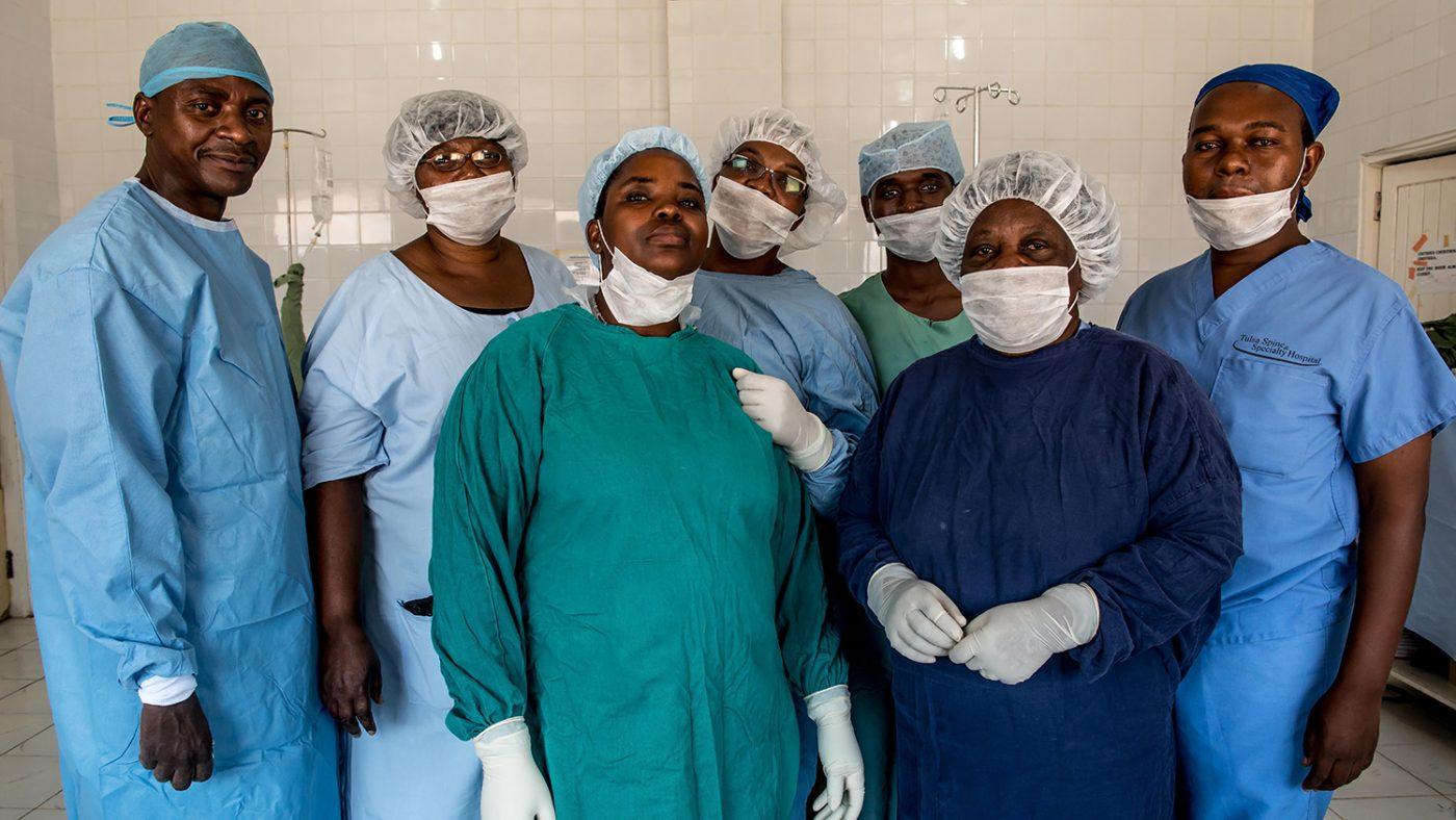 Läkarteamet poserar framför kameran iförda sina operationskläder