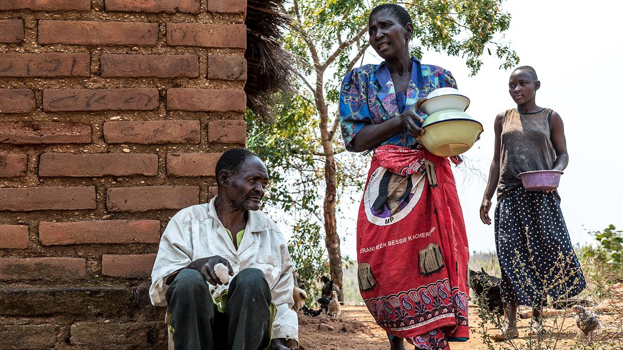 Winesi sitter på marken innan gråstarrsoperationen. Runt om honom utför hans familj olika sysslor.