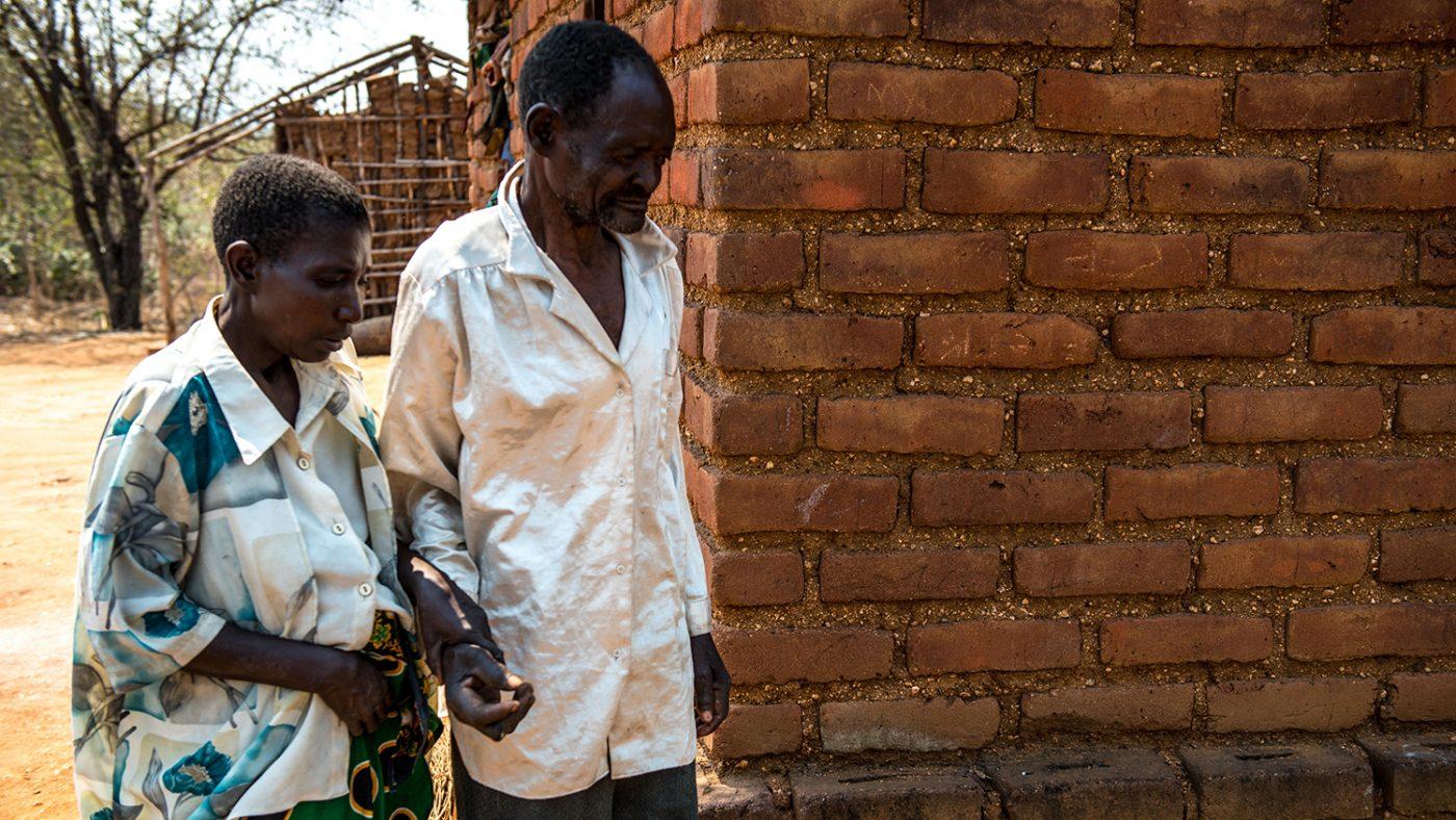 Winesi leds av sin fru utanför deras hus.