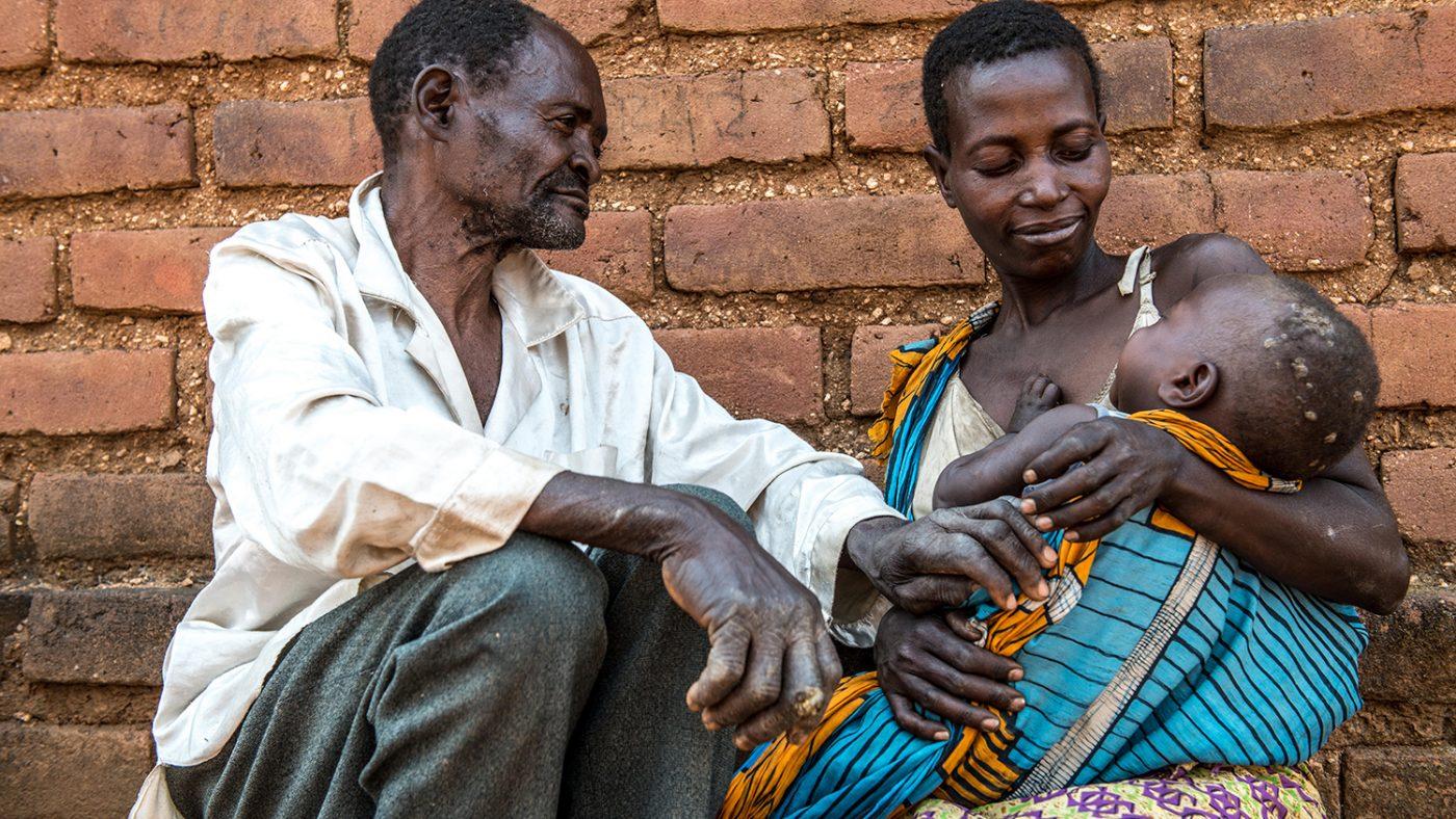 Winesi sitter utanför sitt hus med dotter och barnbarn.