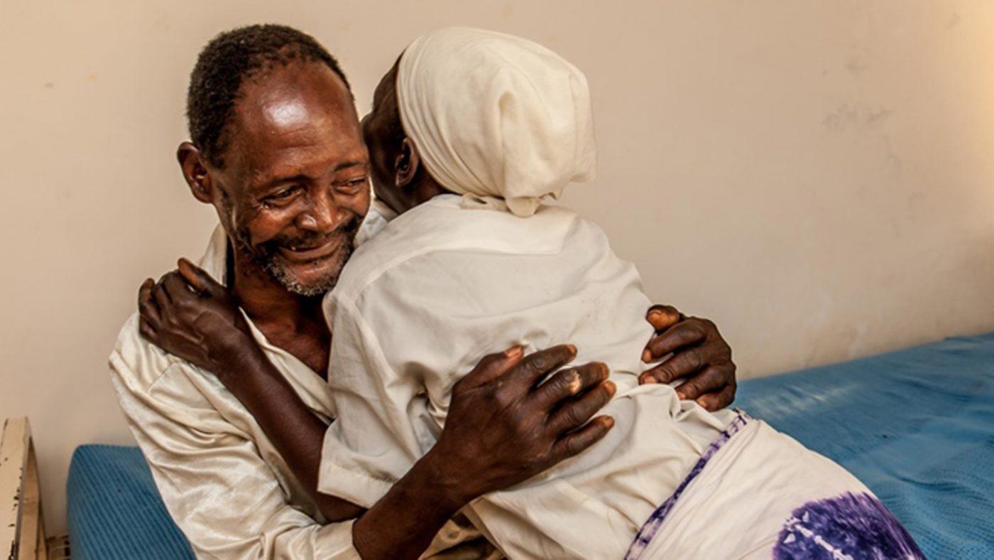 69-årige Winesi kramar sin fru och ler efter att ha genomgått en gråstarrsoperation.