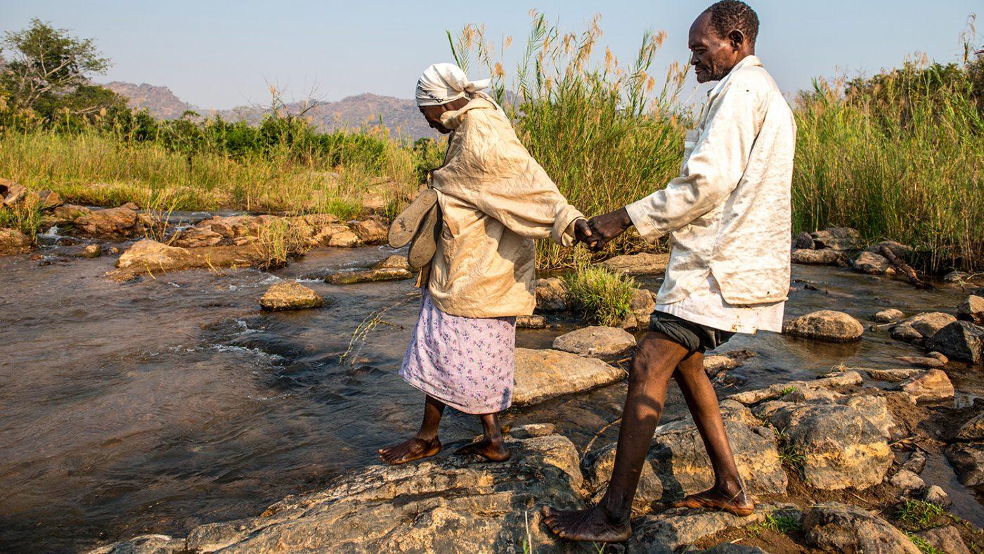 Winesi leds av sin fru över en flod.