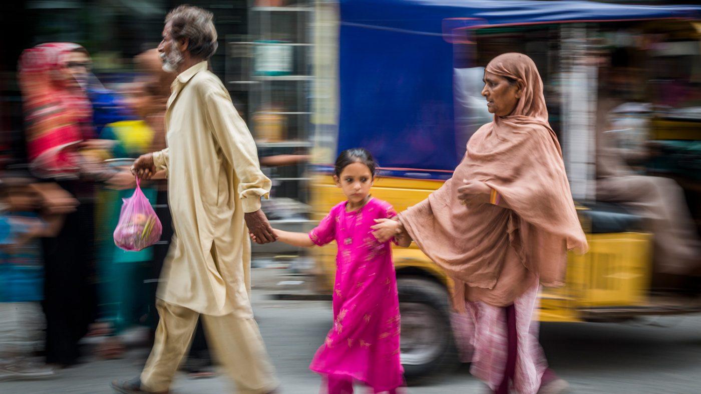 Zamurrad leds av sin dotter och man över en trafikerad väg.
