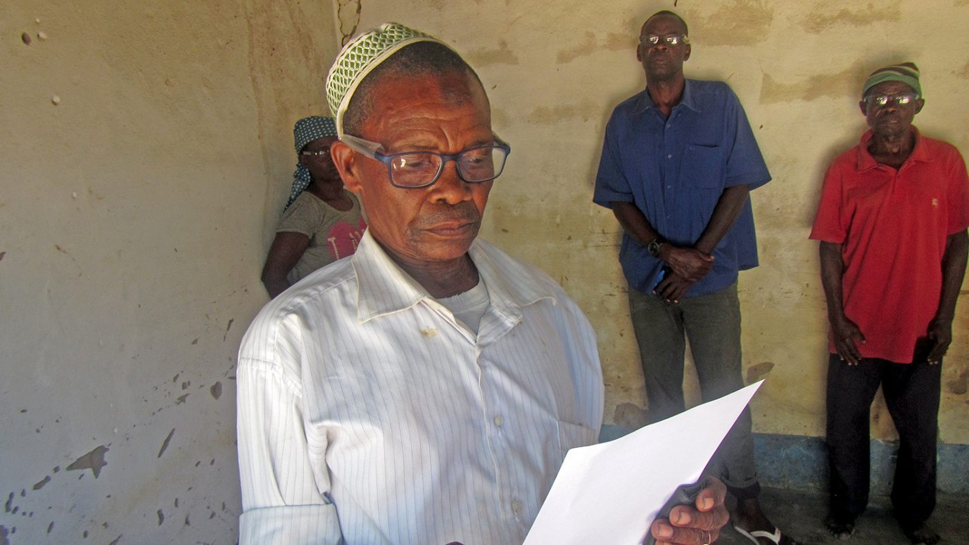 Juma reads from a sheet of paper while wearing his new glasses.