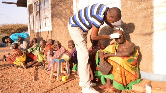 Två sjukvårdare tvättar ögonen på män som är klädda i traditionella afrikanska kläder.