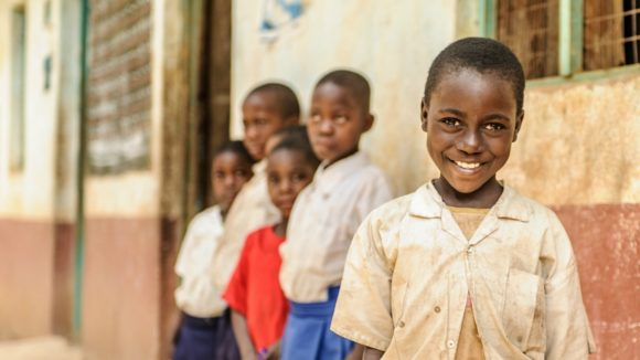 Zuhara from Tanzania stands outside her primary school