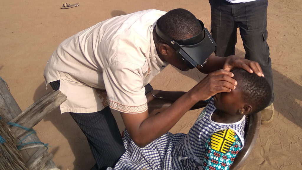 En lokal volontär i Elfenbenskusten lär sig att upptäcka trakom genom att undersöka ögonen på ett barn.