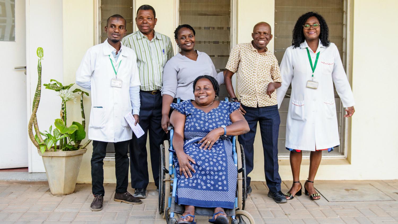 Ledare för organisationer för personer med funktionsnedsättning, personal från Sightsavers och läkare tillsammans med Camilo Morreira utanför ett sjukhus.