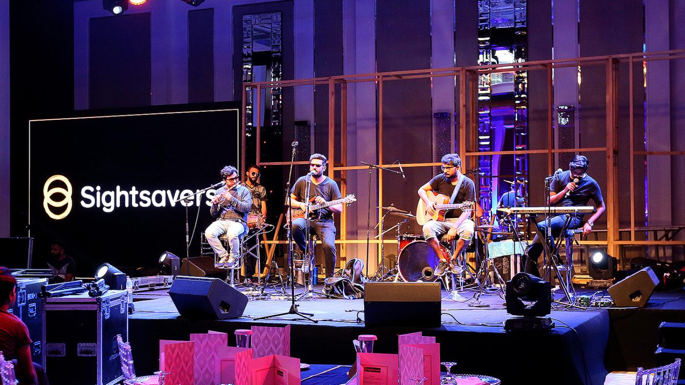 En grupp musiker spelar gitarr på en scen med Sightsavers-banderoller i bakgrunden.