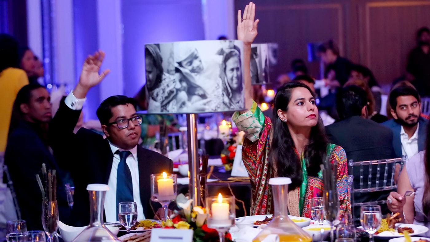 Ett glamoröst par sitter vid ett fint dukat bord. De håller upp händerna i luften för att bjuda under auktionen.