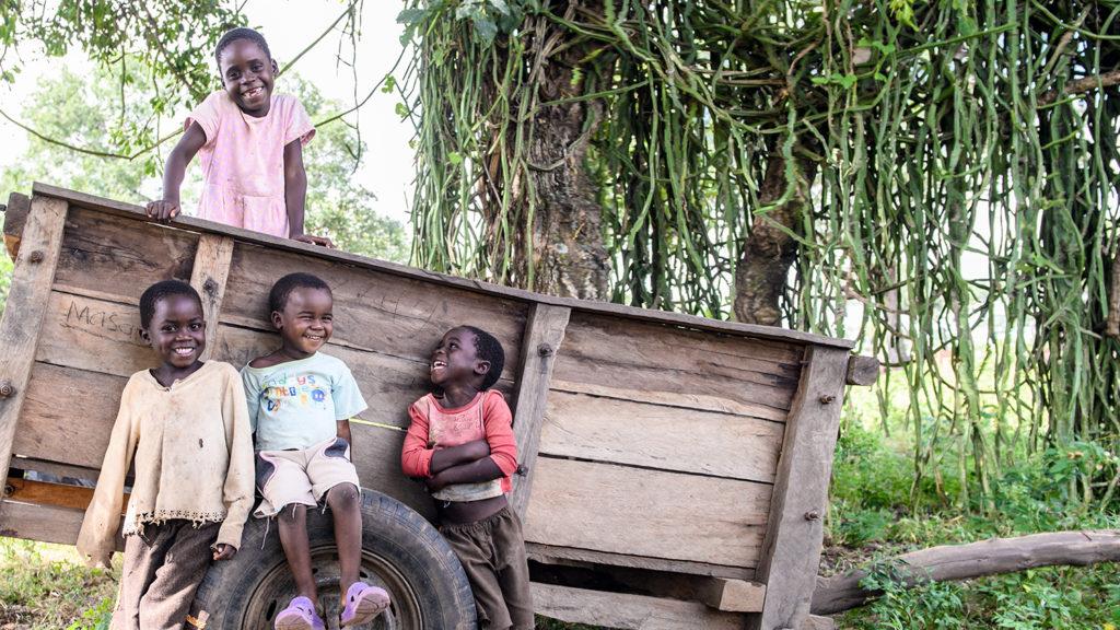 En grupp leende barn står vid en träkärra i Zambia.