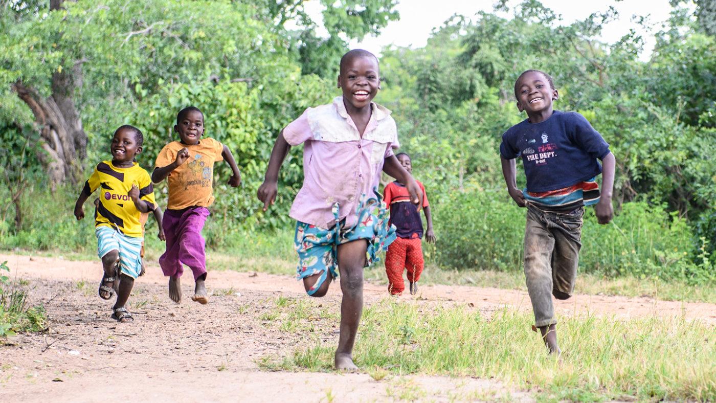 En grupp barn springer leende genom sin hemby.