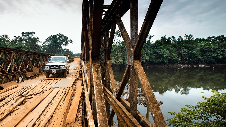 En fyrhjulsdriven jeep korsar en ranglig bro över en flod i regionen Rivercess, Liberia.