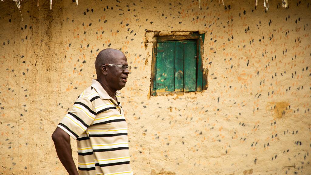 Lincoln Gankpala, iklädd randig T-shirt, står utanför sitt hem i Gorzohn, Liberia.