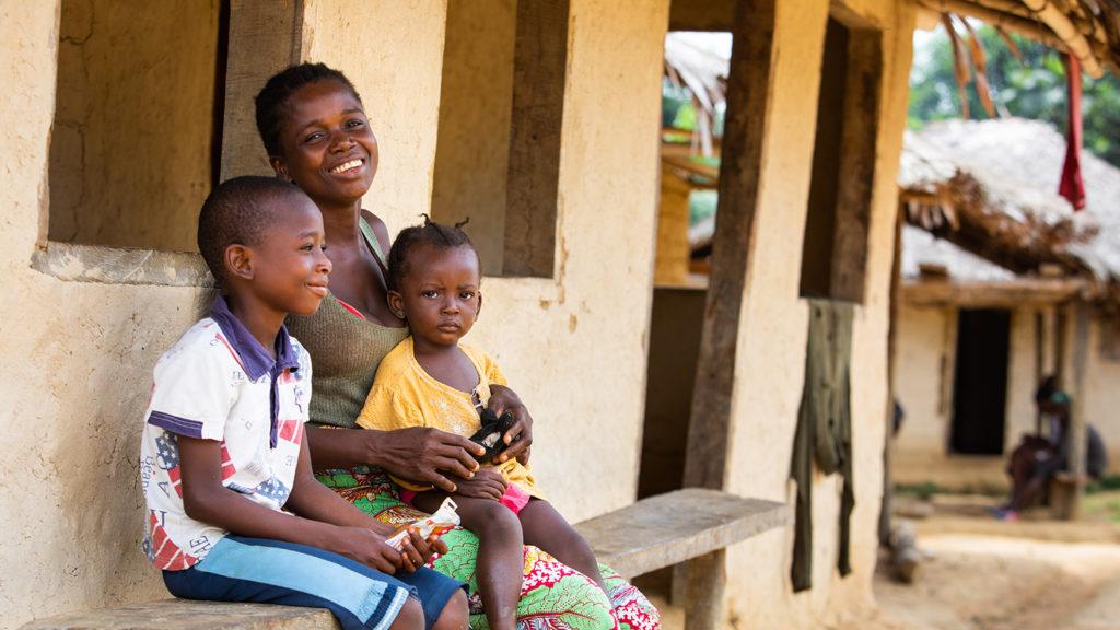 Sia Tamba sitter med sin son och dotter utanför deras hem.