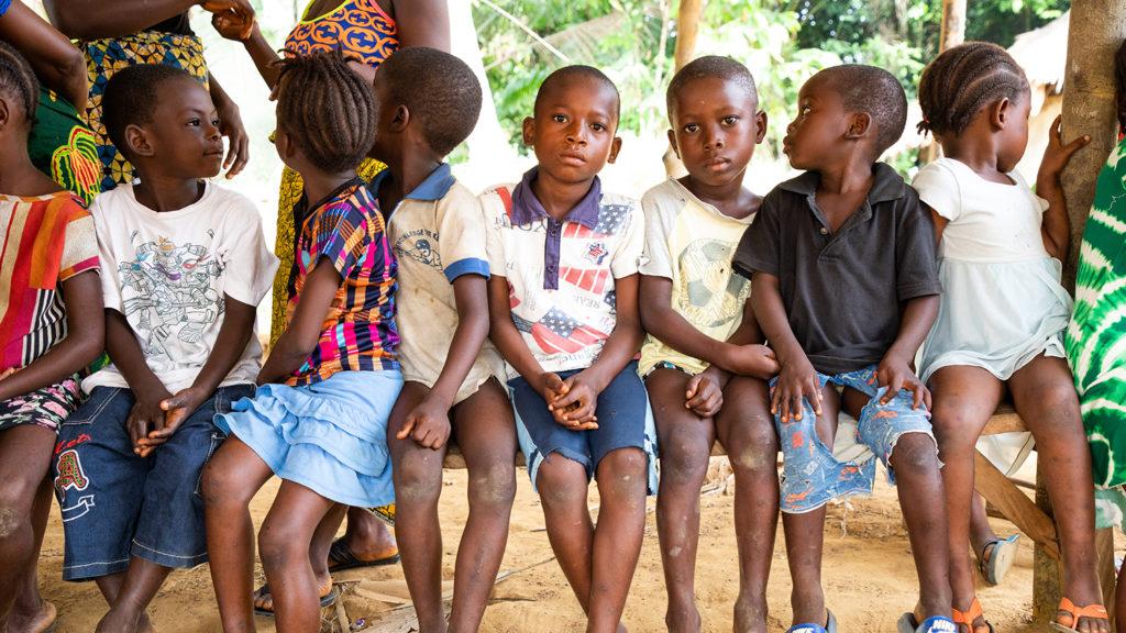 En grupp barn sitter på rad på en bänk i väntan på att undersökas för flodblindhet.