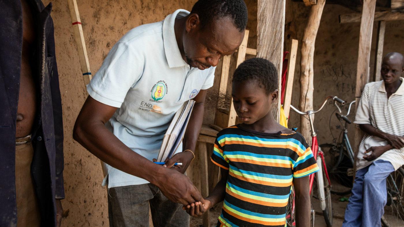 En av våra CDD-volontärer (community-directed distributors) ger medicin till en pojke för att bekämpa flodblindhet