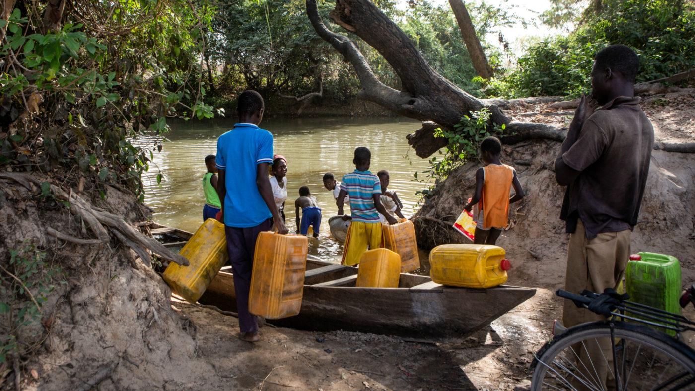 Ett antal män använder sig av stora gula plastdunkar för att hämta vatten i Pru-floden.