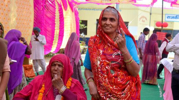 Två kvinnor visar sina pekfingrar efter att ha röstat i Indiens allmänna val 2019.