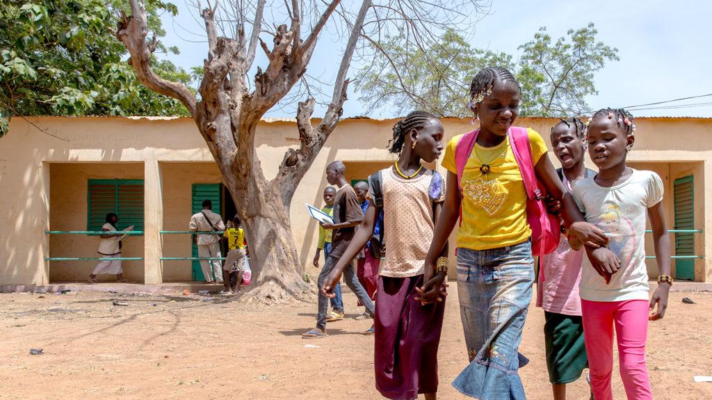 En grupp elever går arm i arm utanför sin skola i Mali.