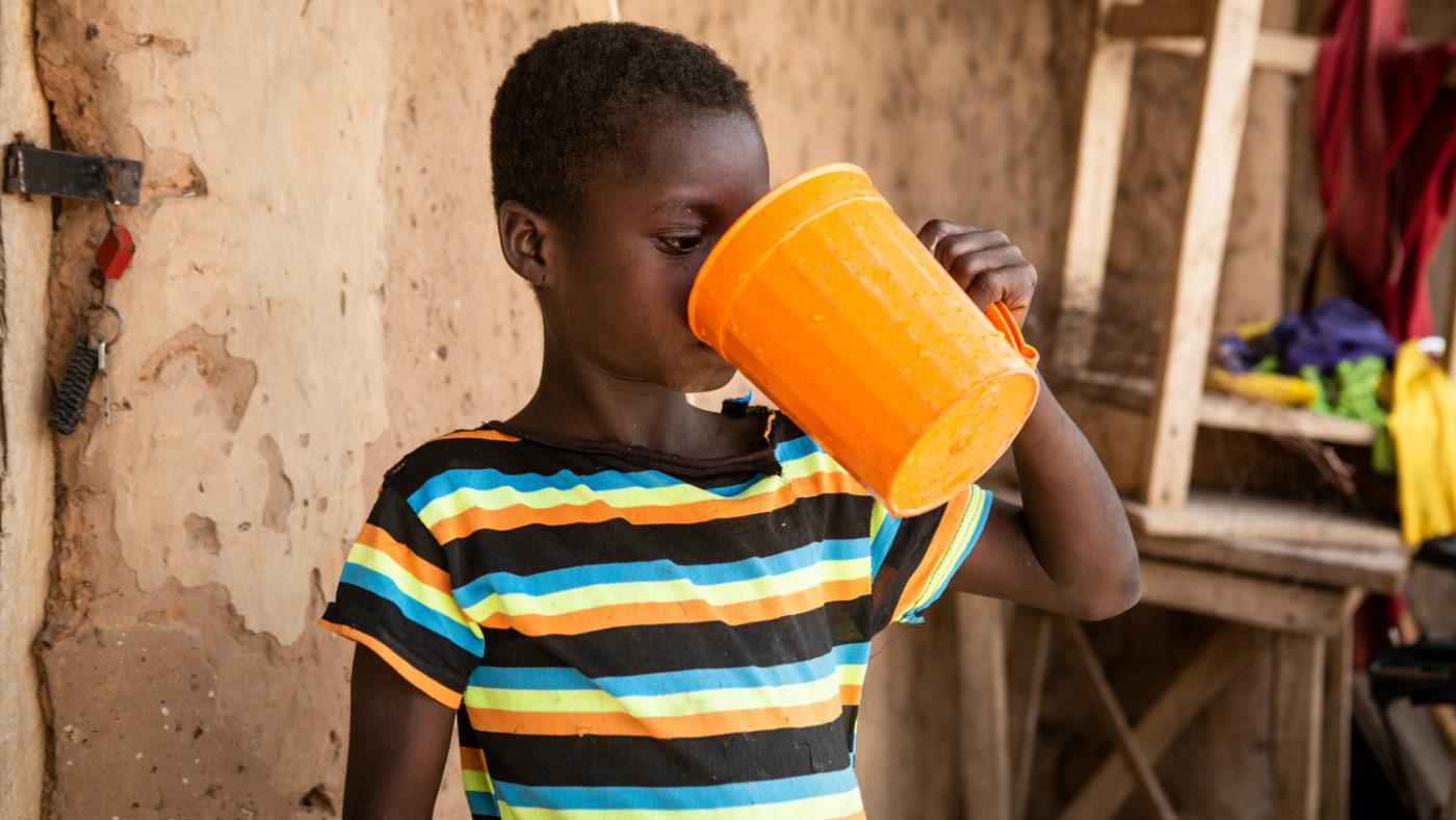 En pojke dricker vatten för att svälja tabletten han fått för att skydda honom mot flodblindhet.