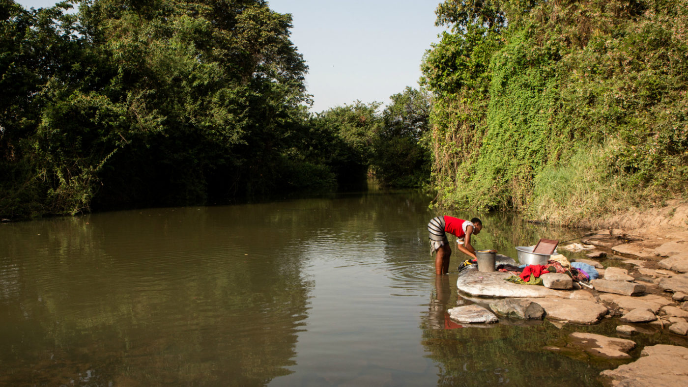 En kvinna tvättar sina kläder i floden Pru i Asubende, Ghana.