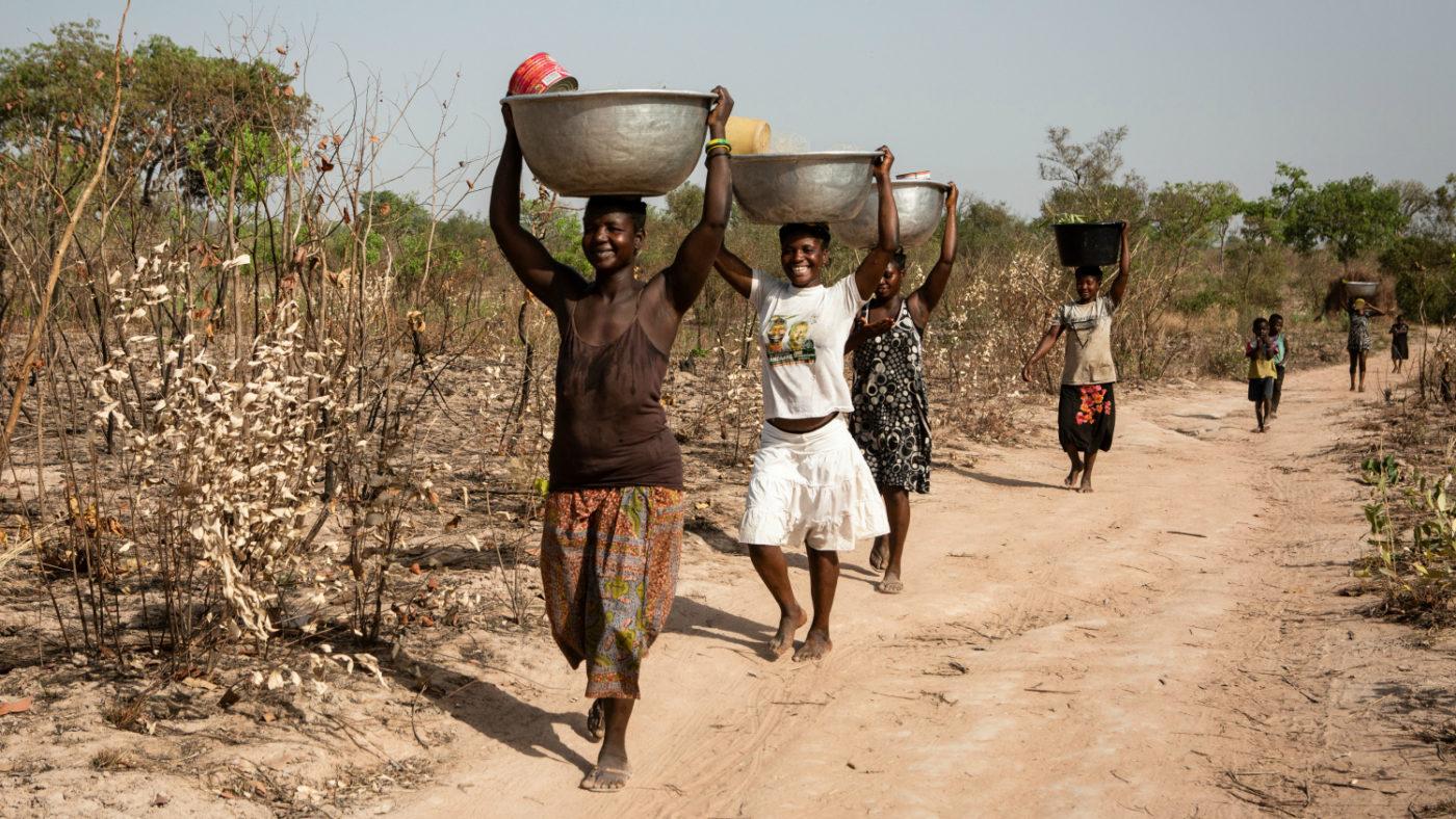 Fyra kvinnor går längs en dammig grusväg. De bär stora ämbar på huvudet för att hämta vatten