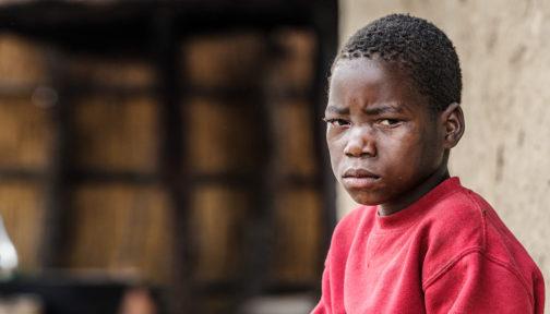 Mwiza sitter utanför sitt hem. Han ser ledsen ut.