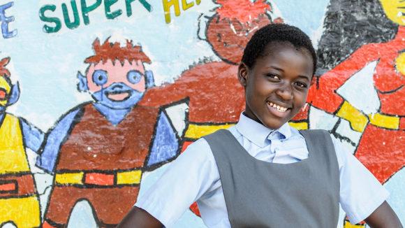 Skolelever ler framför en väggmålning i Zambia.