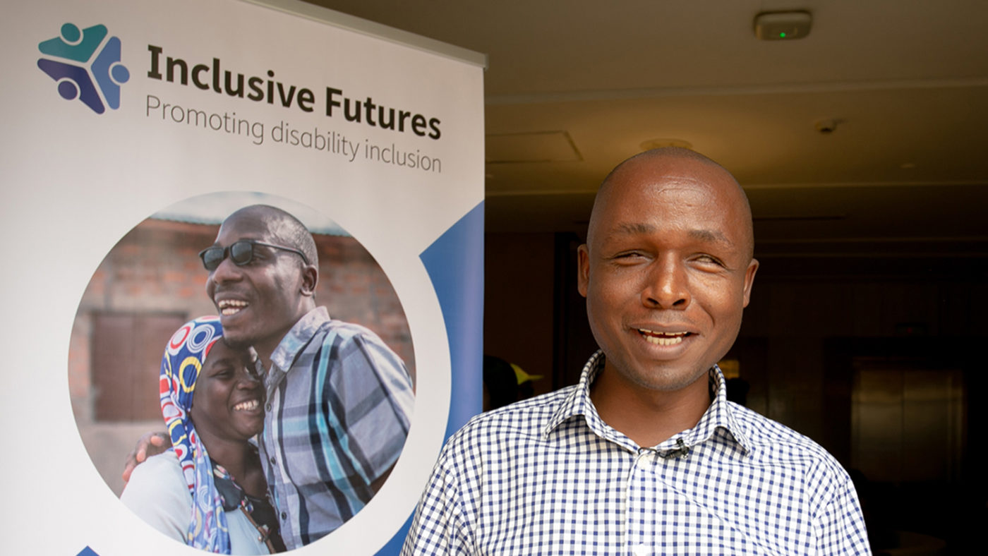 Deus Turyatemba står bredvid en Inclusive Futures-plansch