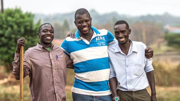 Tre män med käppar står arm i arm.