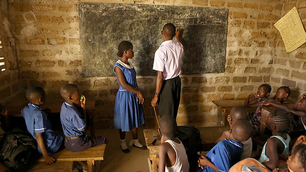 En klar och tydlig bild av ett klassrum i Sierra Leone. Läraren står vid svarta tavlan med en elev medan klasskamraterna tittar på.