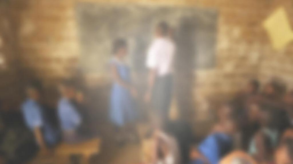 En oskarp bild av ett klassrum i Sierra Leone. Bilden är suddig och otydlig med en vitaktig nyans. Det är svårt att urskilja läraren och svarta tavlan.