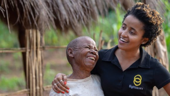 Mercia laughs and celebrates with a trachoma surgery patient after her bandages have been removed.