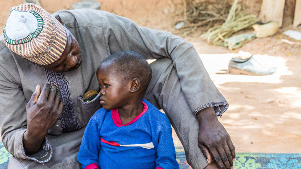 Muzi and his dad sat outside in their village in Nigeria
