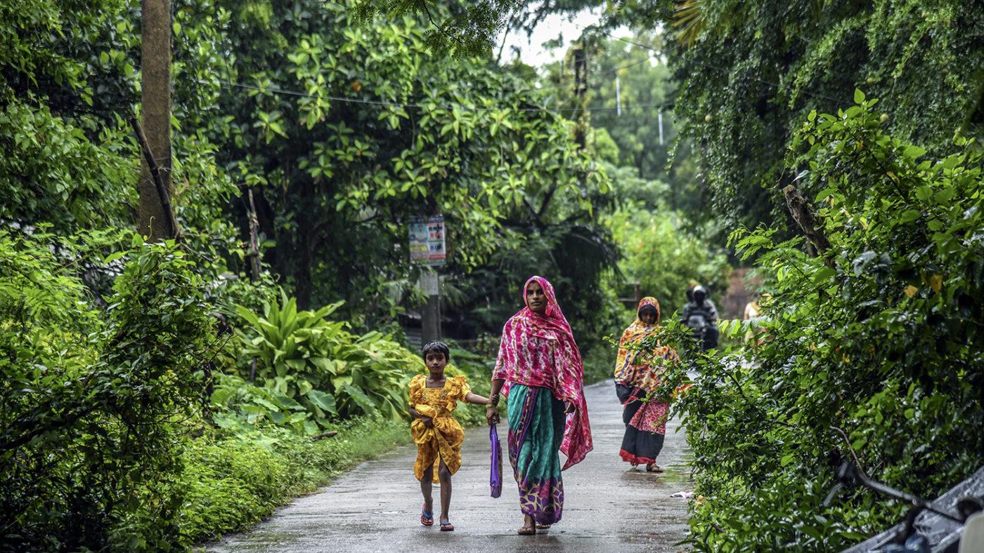 En kvinna och ett barn går på en våt stig under träd.