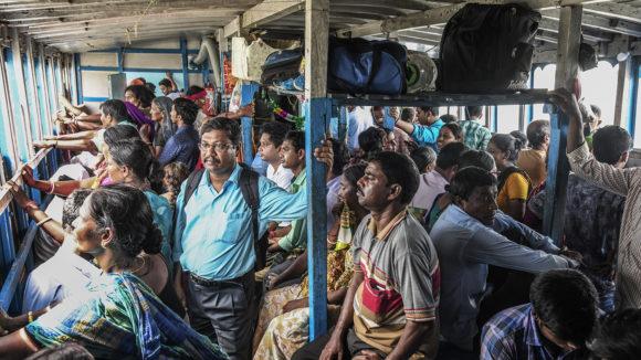 Många människor står ombord på en färja.