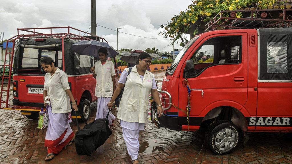 Tre kvinnor går förbi ett par skåpbilar.